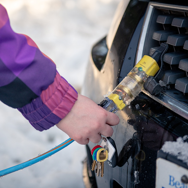 Woman attaching side of Q-Plug together whilst it is plugged into the car's block heater